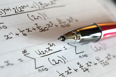 Education. Complex mathematical trigonometry formulae on paper with pen Stock Images