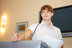 Education. The young guy tells speech from a tribune in an educational room Stock Photography