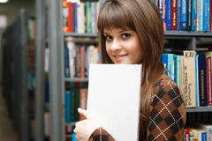 Education. The young girl with the book in a hand against library Royalty Free Stock Photo