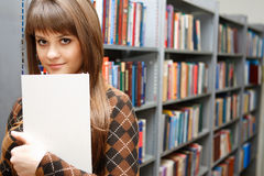 Education. The young girl with the book in a hand against library Royalty Free Stock Images