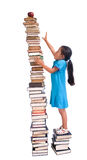 Education. Going to school is your future. Education, learning, teaching. A young girl reaches for an apple and pencil on a tall tower of books. Reaching high Stock Images