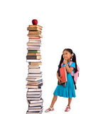 Education. Going to school is your future. Education, learning, teaching. A young girl looks at a tall pile of books Stock Image