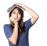 Education. Tired girl holds a notebook on her head on a white background with copyspace Royalty Free Stock Photo