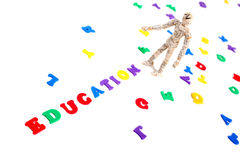 Education. Manikin covered in newspaper clippings standing at letters spelling education stock photo