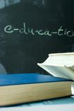 Education. Piled books against a blackboard with 'education' written on it Stock Images