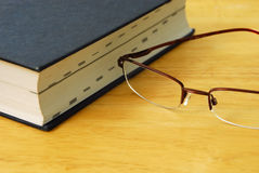 Education. This is a shot of a dictionary and a pair of glasses Stock Photo