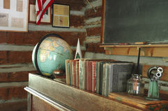 Education. A teacher's desk and a chalkboard in an old-fashioned one-room schoolhouse stock image