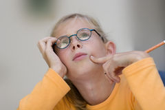 Education. Girl thinking with a pencil in her hand Royalty Free Stock Photos