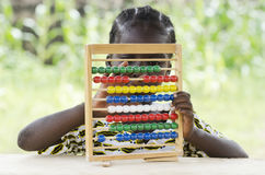 Education for Africa: Little african school girl sitting at school. Little african girl counting on abacus frame on blurred background Stock Images