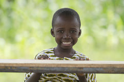 Education for Africa symbol, little African boy sitting in school. Little african boy sitting at wooden table and smiling at camera with blurred background Royalty Free Stock Photo