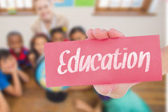 Education against cute pupils and teacher in classroom with globe. The word education and hand showing card against cute pupils and teacher in classroom with stock photography