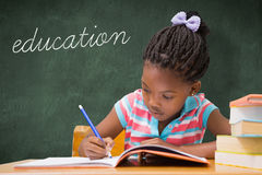 Education against green chalkboard. The word education and cute pupils writing at desk in classroom  against green chalkboard Stock Photo