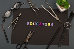 Education of architecture - black paper, text `Education` of wooden letters, engineering tools, eyeglasses, scissors. And watch on grey background stock photo