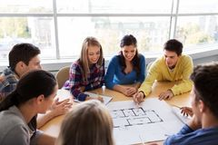 Group of smiling students with blueprint stock photography