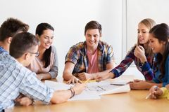 Group of smiling students with blueprint stock image