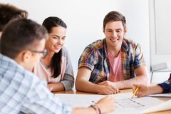 Group of smiling students with blueprint royalty free stock photo