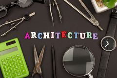Education of architecture - text `architecture` of wooden letters, engineering tools, magnifying glass, eyeglasses, calculator. Scissors and watch on black royalty free stock photography