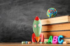 Education and back to school concept. cardboard rocket, books and chalks in front of classroom blackboard.  royalty free stock photography