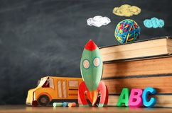 Education and back to school concept. cardboard rocket, bus, books and chalks in front of classroom blackboard.  stock photo