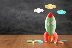 Education and back to school concept. cardboard rocket and chalks in front of classroom blackboard.  royalty free stock photos