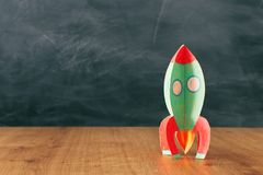 Education and back to school concept. cardboard rocket in front of classroom blackboard.  royalty free stock image