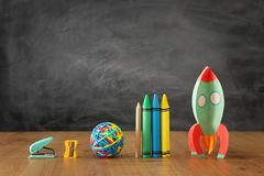 Education and back to school concept. cardboard rocket and pencils in front of classroom blackboard.  royalty free stock image