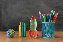 Education and back to school concept. cardboard rocket and pencils in front of classroom blackboard.  royalty free stock photos