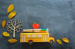 Education and back to school concept. Top view photo of cardboard school bus, apple and pencils next to tree with autumn dry. Leaves over classroom blackboard stock image