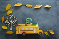 Education and back to school concept. Top view photo of cardboard school bus and pencils next to tree with autumn dry leaves over. Classroom blackboard stock image