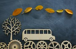 Education and back to school concept. Top view photo of school bus over wooden gears as concept of success and achievement and. Classroom blackboard background stock photography