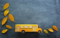 Education and back to school. Top view photo of cardboard school bus next to autumn dry leaves over classroom blackboard. Background royalty free stock photography