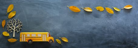 Education and back to school. Top view photo of cardboard school bus next to autumn dry leaves over classroom blackboard. Background royalty free stock image