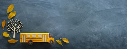 Education and back to school. Top view photo of cardboard school bus next to autumn dry leaves over classroom blackboard. Background stock photography