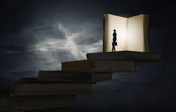 Education benefit. Big old opened book and miniature of businesswoman Royalty Free Stock Photo