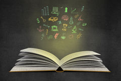 Education and business objects. Idea concept with open book, illuminated colorful business sketch on wall. Creative business sketching. Abstract image containing Stock Images