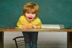 Education. Cheerful smiling child at the blackboard. Hard exam. Schoolchild. Happy smiling pupils drawing at the desk. Education. Cheerful smiling child at the royalty free stock photos