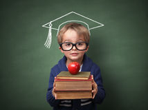 Education. Child holding stack of books with mortar board chalk drawing on blackboard concept for university education and future aspirations Royalty Free Stock Images