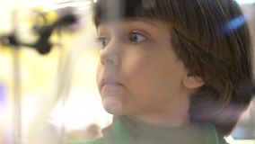 Education, childhood, emotion, expression and people concept. Boy looks at marbles inside run machine which reflect his. Head, closeup view. portrait of a cute stock video footage