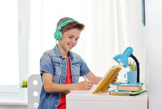 Student boy in headphones writing to notebook Stock Images