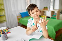 Boy doing homework and counting using fingers. Education, childhood and school concept - happy student boy counting using fingers at home royalty free stock image