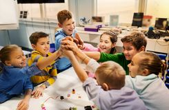 Happy children making high five at robotics school. Education, children, technology, science and people concept - group of happy kids building robots and making Stock Photography