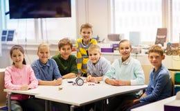 Happy children building robots at robotics school. Education, children, technology, science and people concept - group of happy kids building robots at robotics stock photo