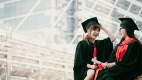 EDUCATION IN CITY. Two girls in black gowns and hold diploma certificate sitting and smiling with happy graduated stock photo