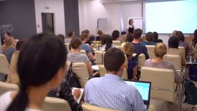 Education classroom blur background of university students sitting in a lecture hall or seminar room with teacher. View. From behind audience at business stock video