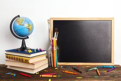 Education composition from a clean chalkboard, a globe, a stack of books and school supplies. Copy space for text. The concept of the teacher`s day royalty free stock image