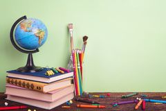 Education composition with a globe, a stack of books and school supplies on a green background. Copy space for text. The concept of the teacher`s day stock photography