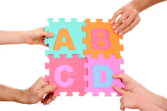 Education concept. Hands holding puzzle with ABCD letters isolated on white Stock Photography
