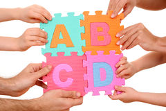 Education concept. Hands holding puzzle with ABCD letters isolated on white Stock Image
