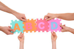 Education concept. Hands holding puzzle with ABCD letters isolated on white Royalty Free Stock Images