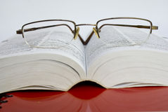 Education concept. Spectacles between opened dictionary pages Royalty Free Stock Image